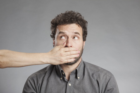 mouth couple: Womans hand covering mature mans mouth Stock Photo
