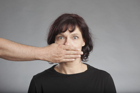 Mans hand covering mature womans mouth