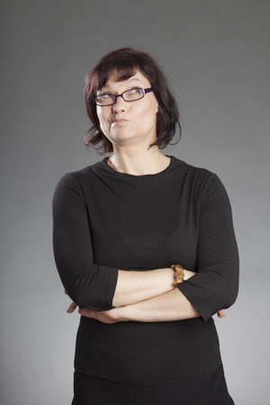 sceptical: Mature brunette woman wearing glasses standing with hands folded making faces against gray background