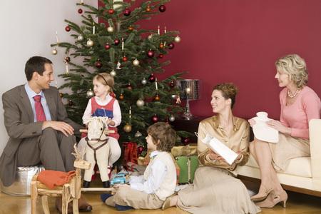 Family sitting next to Christmas tree photo