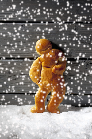 Christmas gingerbread man on heap of snow against wooden background photo