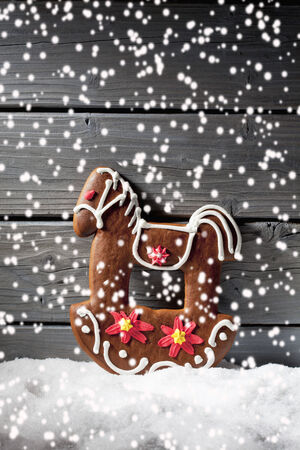 Snowfall with christmas gingerbread horse on heap of snow against wooden background photo