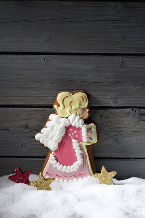Gingerbread christmas angel star shaped decorations on heap of snow against wooden background photo