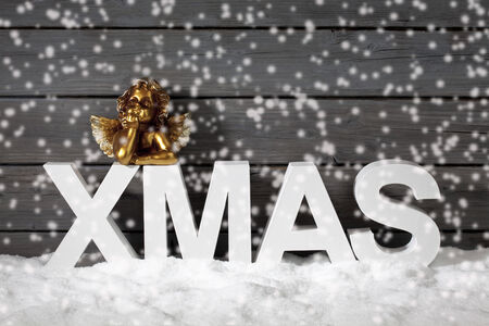 Capital letters forming the word xmas and golden putto figurine on pile of snow against wooden wall snow is falling