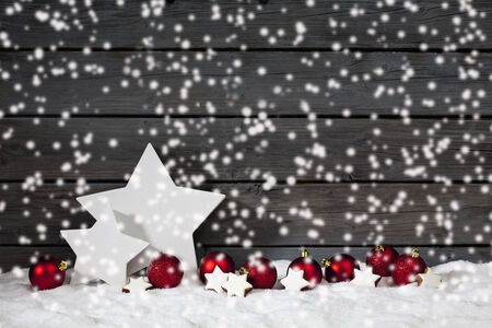 Star shaped christmas decoration christmas bulbs cinnamon stars on pile of snow against wooden wall snow is falling photo