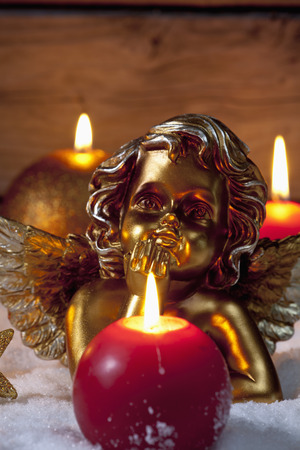 putto: Golden putto with burning candles on pile of snow