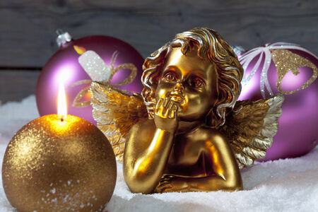 angel figurine: Christmas bulbs burning candle golden putto on pile of snow Stock Photo