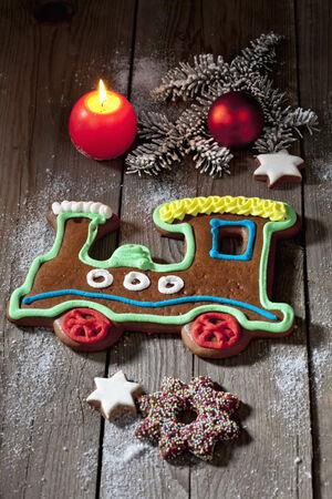Christmas gingerbread train with candle cinnamon stars pine twig christmas bulb on wooden floor photo
