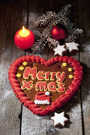 Christmas gingerbread heart with candle cinnamon stars pine twig christmas bulb on wooden floor photo