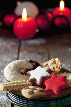 Selection of christmas cookies on plate on wooden floor burning candles in background photo