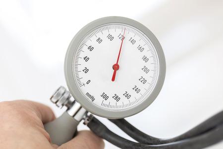 Hand holding blood pressure gauge close up photo