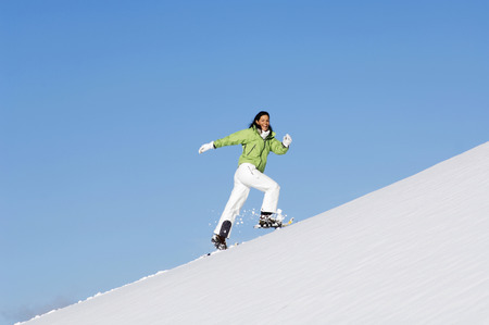 snowshoes: Woman running uphill with snowshoes