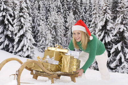 Austria, Salzburger Land, Altenmarkt, Young woman pushing wooden sledge with Christmas presents photo