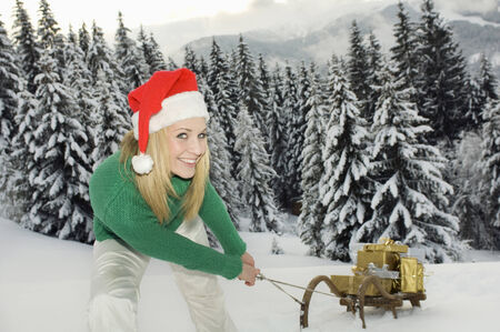 hair wrapped up: Austria, Salzburger Land, Altenmarkt, Young woman pulling wooden sledge with Christmas presents