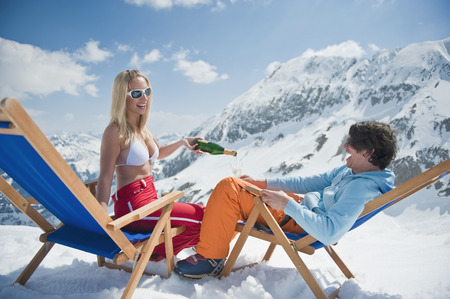 Austria, Salzburger Land, Couple sitting in deck chairs, woman holding champagne bottle photo