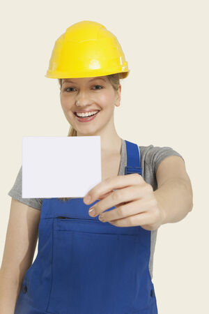 workwoman: Construction worker wearing hardhat  and holding paper smiling Stock Photo