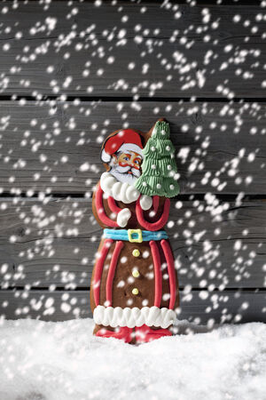 Snowfall with gingerbread santa claus on heap of snow against wooden background photo