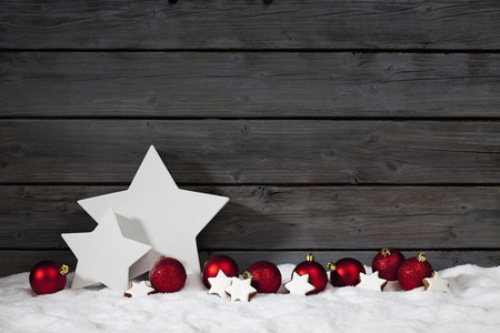 Star shaped christmas decoration christmas bulbs cinnamon stars on pile of snow against wooden wall