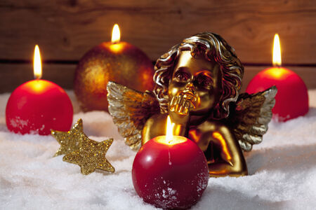 putto: Golden putto with burning candles and star shaped christmas decorations on pile of snow