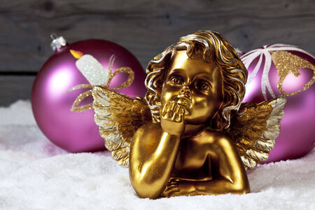 Christmas bulbs golden putto on pile of snow