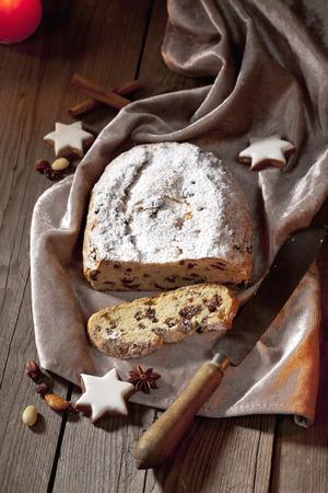 Christmas stollen with cinnamon stars cinnamon sticks nuts knife on velvet napkin photo