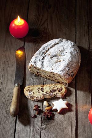 Christmas stollen with candle cinnamon stars nuts on velvet napkin photo