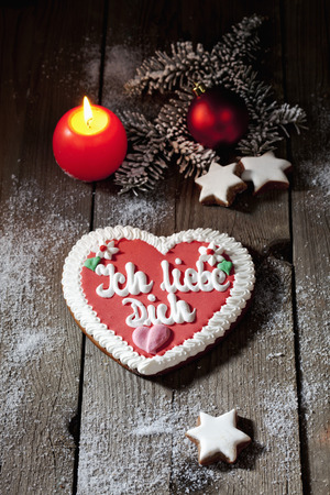 Gingerbread heart with candle cinnamon stars pine twig christmas bulb on wooden floor photo