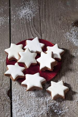 Stack of cinnamon stars on plate on wooden floor photo