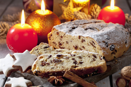 Christmas stollen with candles cinnamon stars cinnamon sticks pine twig nuts on wooden board photo