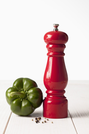 pepper grinder: Green bell pepper and red pepper grinder on white wooden table