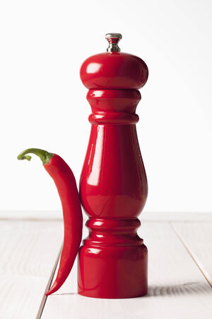 pepper grinder: Red chili and red pepper grinder on white wooden table Stock Photo
