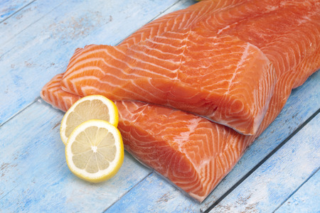salmonidae: Raw salmon fillet and lemon slices on blue wooden table
