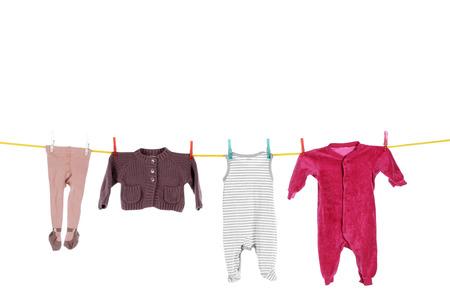 ropa colgada: Ropa del bebé que cuelga en la línea de lavado