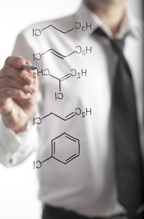 clarifying: Chemist writing H2O formula on whiteboard Stock Photo