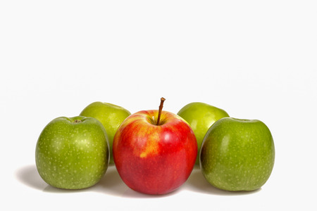 Red apple laying in group of green apples on white background