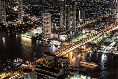 Bankok skyline by night highway and river traffic photo