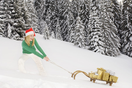 Austria, Salzburger Land, Altenmarkt, Young woman pulling wooden sledge with Christmas presents photo