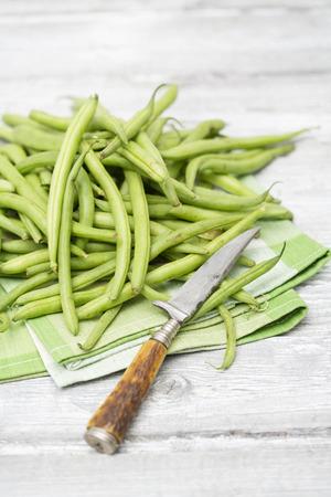 long bean: Raw green beans (Phaseolus vulgaris) antique knife on cloth napkin
