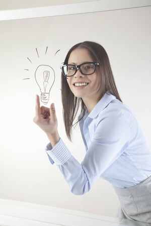 Business woman with drawn light bulb on whiteboard smiling photo