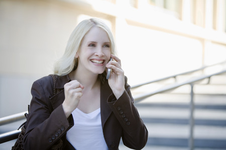 clenching: Young woman using mobile phone, clenching her fist, portrait Stock Photo