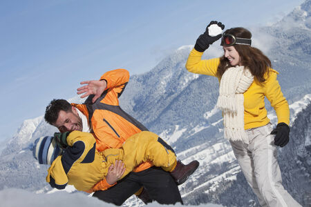 Germany, Bavaria, Family having snowball fight photo