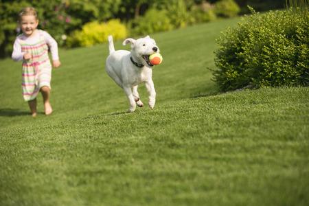 Junges Mädchen mit Hund im Garten spielen