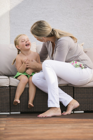 tickling: Mother helping daughter to dress Stock Photo