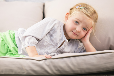 sceptic: Young girl lying on couch Stock Photo