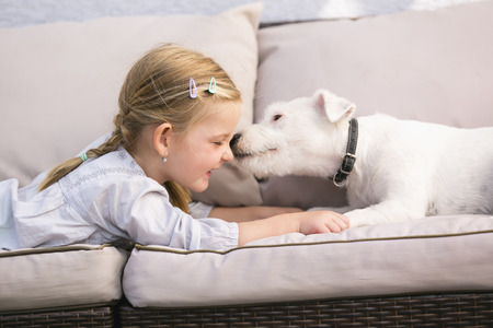 Young girl lying with pet dog on couch