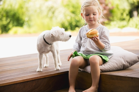 dog eating: Young girl sitting on wooden steps with her dog eating doughnut