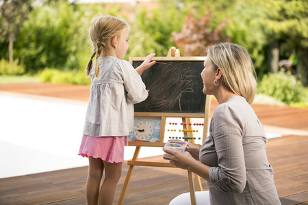 Young girl and mother playing outside wiping chalkboard off photo