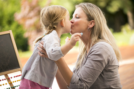 Young girl and mother playing outside kissing each other Stock Photo