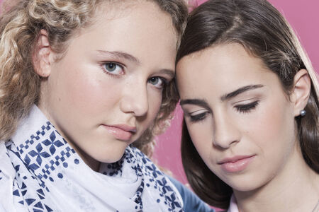 Two girls against pink background photo