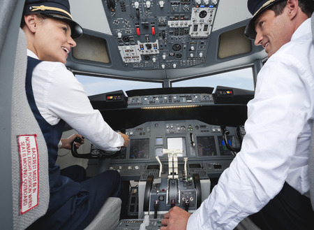 Pilot and co-pilot driving airplane in cockpit smiling 스톡 콘텐츠